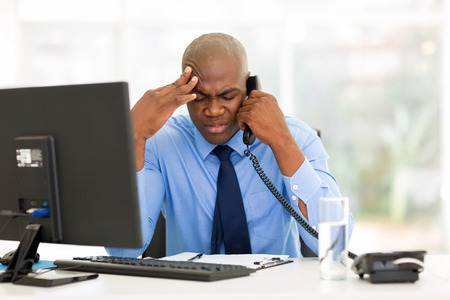 stressed businessman talking on landline phone in modern office