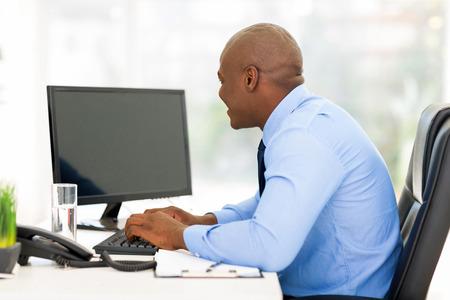 近代的なオフィス内のコンピューターに取り組んでいる若いアフロ アメリカ人実業家 写真素材