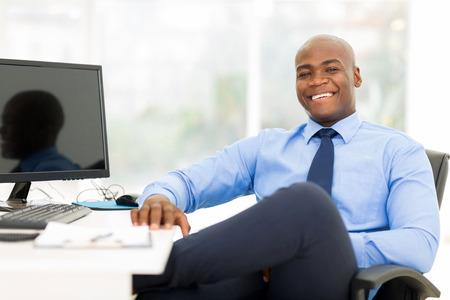 relajado: hombre de negocios negro relajado sentado en la oficina moderna