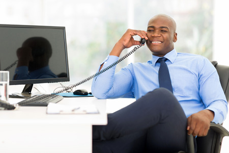 handsome african american businessman using landline phone