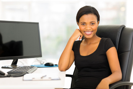 african business woman: relaxed african businesswoman sitting in modern office