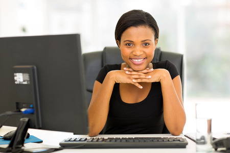 portrait of happy young african business woman sitting in office 스톡 콘텐츠