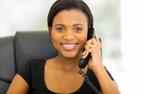 business woman phone: happy african businesswoman talking on phone in the office Stock Photo
