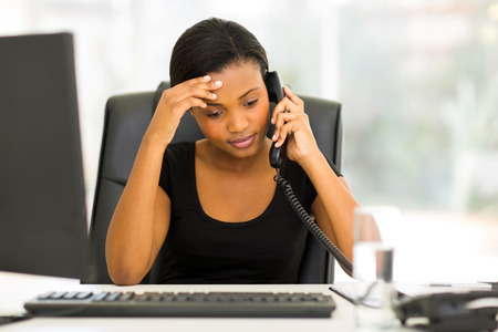 office attire: tired black businesswoman using landline phone in office Stock Photo