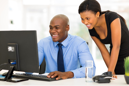 successful african secretary with her boss working on computer