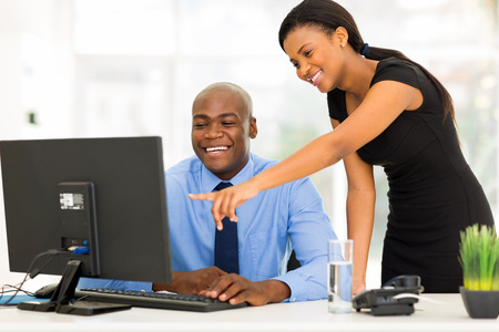 african american male: african businesspeople working at the office on a computer