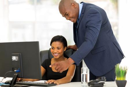 secretarias: amigable jefe africano guiar a su nuevo empleado con su trabajo Foto de archivo