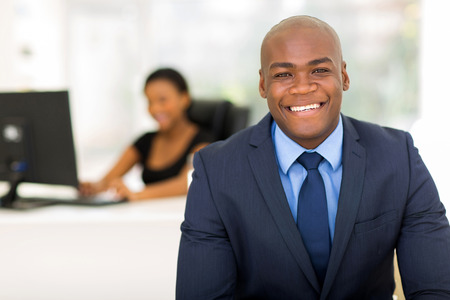professional portrait: cheerful african american businessman in office with colleague on background