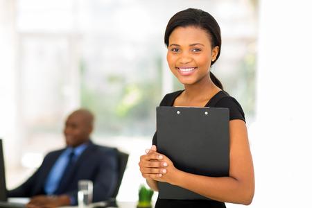mooie zakenvrouw die klembord met collega op de achtergrond