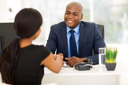 agente comercial: éxito africano americano empresario apretón de manos con el cliente en la oficina