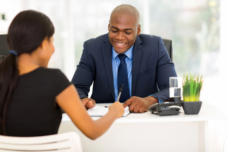 back view of african woman signing employment contract in office