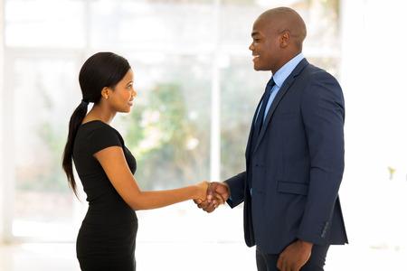 ejecutivos: sonriente hombre de negocios africano apret�n de manos con la empresaria joven en la oficina Foto de archivo