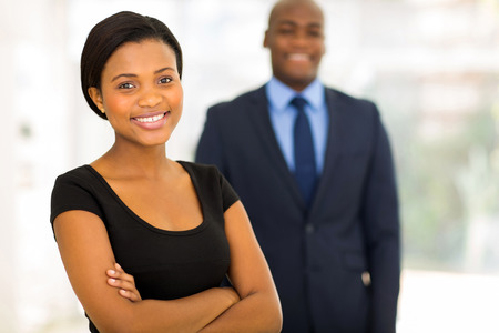 happy workers: beautiful young african businesswoman standing in front of her colleague Stock Photo