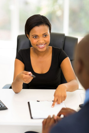 male and female: professional african businesswoman giving her business partner a contract for signing
