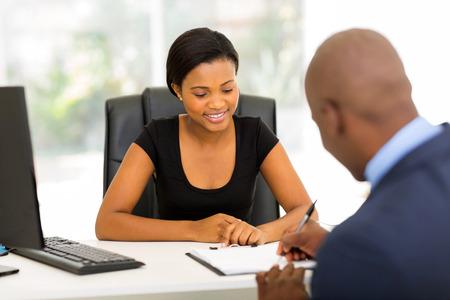 contrato de trabajo: vista posterior del africano contrato empresario firma en la oficina