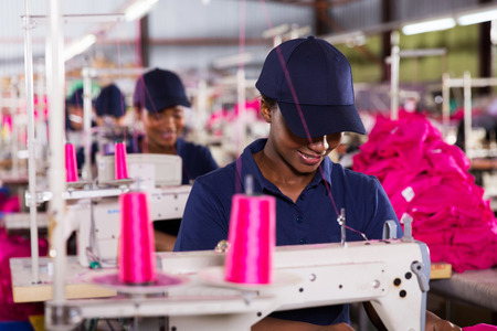 smiling african worker sewing in clothing factory