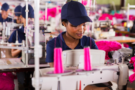 machinist: african clothing factory worker sewing with colleagues on background