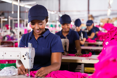 young african textile worker sewing on production line Standard-Bild