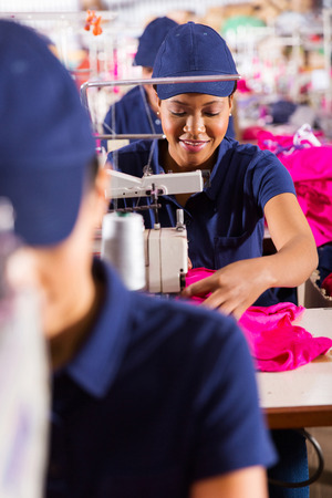 beautiful african textile worker using sewing machine photo