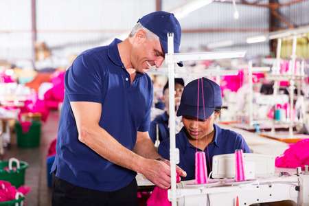 clothing factory quality controller checking stitch on production line photo