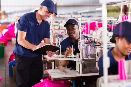 senior supervisor taking score from machinist in clothing factory photo