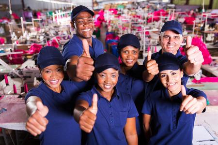groep gelukkige kleding fabriek medewerkers thumbs up Stockfoto