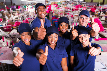 group of happy clothing factory co-workers thumbs up Standard-Bild