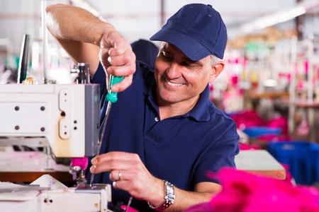 maquina de coser: Mecánico mayor reparación de máquinas de coser industriales en fábrica Foto de archivo