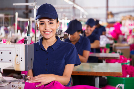 textile industry: beautiful young textile machinist using sewing machine in clothing factory