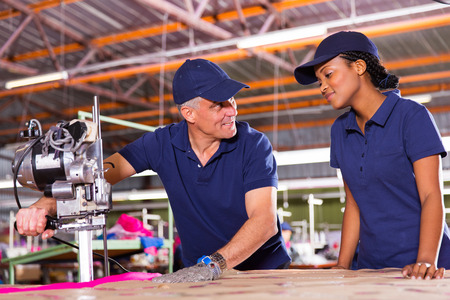 cutting machine is: friendly senior cutter teaching young worker cutting fabric