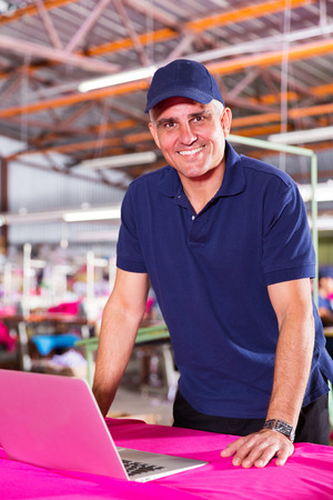 blue collar: happy middle aged textile factory worker using computer Stock Photo