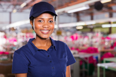 pretty young african female blue collar worker inside clothing factory