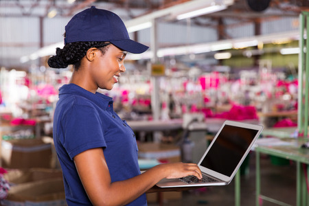 side view of clothing factory manager using laptop computer photo