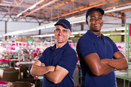portrait of happy textile factory workers with arms crossed