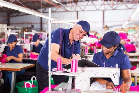 senior textile factory supervisor taking score from machinist