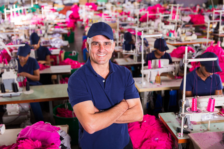above view of senior clothing factory supervisor with arms crossed photo
