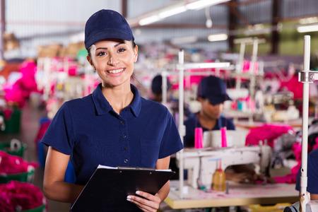 machinist: portrait of pretty female textile worker holding clipboard