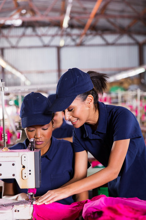 machinist: friendly young woman teaching new machinist to sew Stock Photo