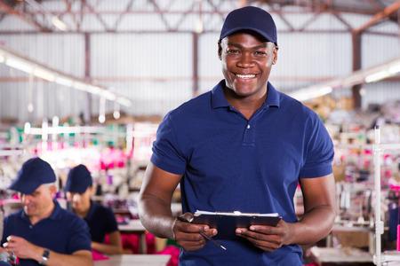 industria textil: guapo afroamericano trabajador textil que sostiene un sujetapapeles