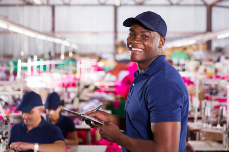 production area: cheerful african textile factory worker in production area Stock Photo