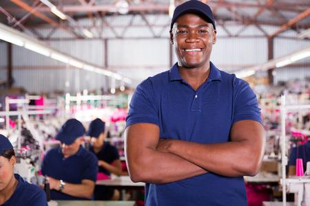 supervisores: apuesto africano supervisor de la fábrica americana con los maquinistas en el fondo Foto de archivo