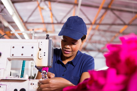 pretty young african worker sewing in clothing factory photo