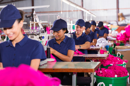 textile industry: group multiracial factory workers sewing in clothing factory