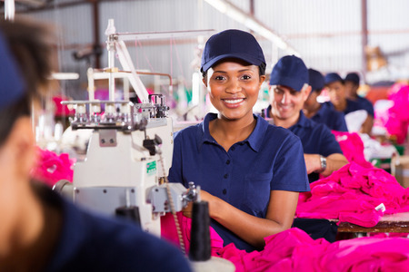 machinist: pretty african sewing machinist working in clothing factory