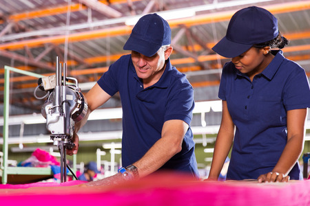 teaching material: senior textile worker teaching new employee about cutting material Stock Photo