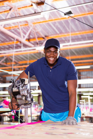 portrait of african american textile factory worker using fabric cutter photo