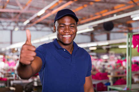 cheerful african american textile worker giving thumb up photo