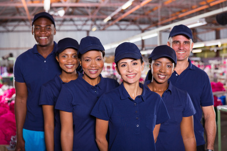 group of happy clothing factory workers inside production area