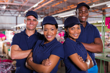 textile industry: happy textile factory co-workers with arms crossed