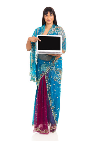 pretty indian woman in sari pointing at laptop screen on white background photo